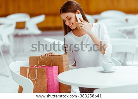 Beautiful young woman in white blouse talking on a mobile phone and drinking coffee while resting in cafe after doing shopping - stock photo