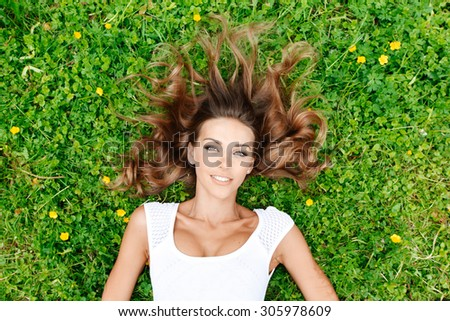 beautiful young woman in white dress lying on grass - stock photo