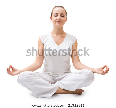 Beautiful young woman in white dress meditating - stock photo