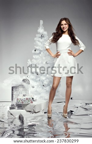 beautiful young woman in white dress next to christmas tree holding presents  - stock photo