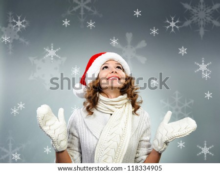Beautiful young woman in white gloves and scarf under snowflakes