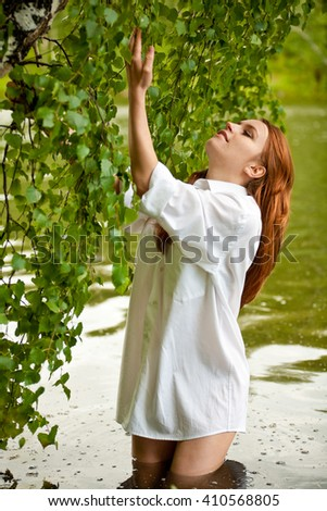 Beautiful young woman in white shirt standing knee-deep in water - stock photo