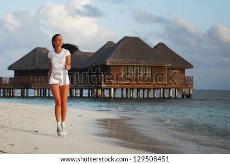 Beautiful young woman in white sportswear running on beach - stock photo