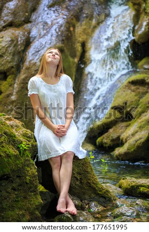 Beautiful young woman in white sundress stopped to rest and dream near the waterfall among the mossy stones  - stock photo
