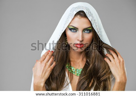 Beautiful young woman in white tunic Arabic, on gray background