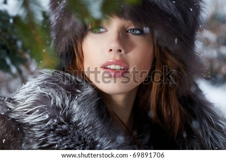 Beautiful young woman in winter forest - stock photo