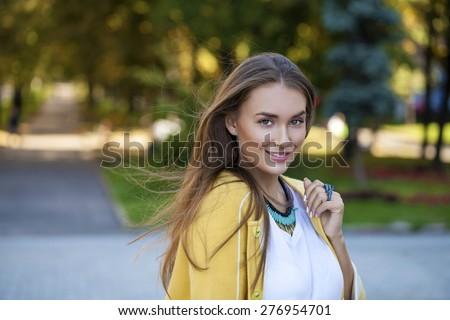 Beautiful young woman in yellow coat in autumn street - stock photo