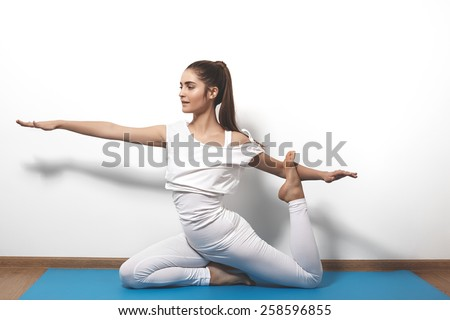 Beautiful young woman in yoga posing on a studio background. Nice sport hairstyle like pony tales. Girl in white clothes for fitness and pilates. Perfect shapes, fit and strong body in asana - stock photo