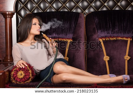 Beautiful young woman inhaling hookah. girl smoking shisha lying on sofa in cafe - stock photo
