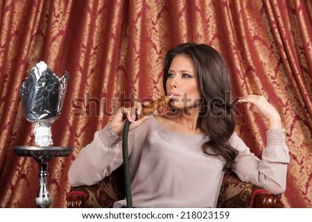 Beautiful young woman inhaling hookah. girl smoking turkish shisha and looking sideways - stock photo