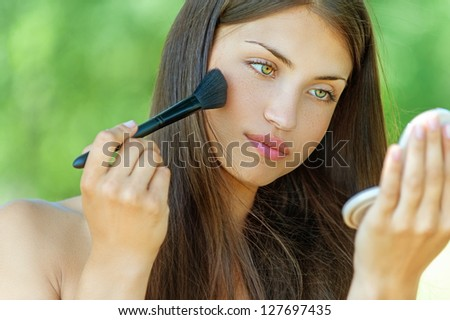Beautiful young woman is brushed powder on face in mirror, against background of summer green park. - stock photo