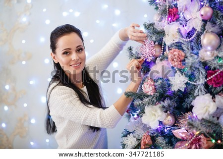 Beautiful young woman is decorating a Christmas tree in the house. Merry Christmas and New Year. - stock photo