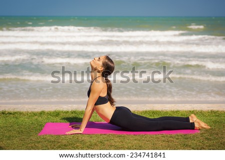 Beautiful young woman is doing yoga near the sea. Pose dog muzzle up. - stock photo