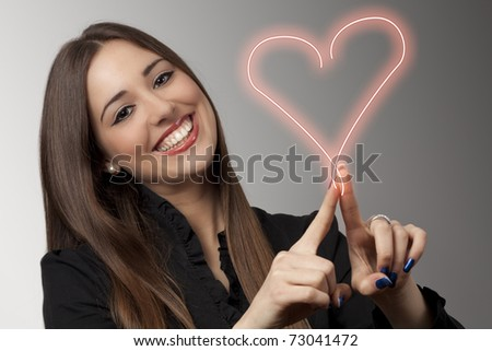 Beautiful young woman is drawing heart - stock photo