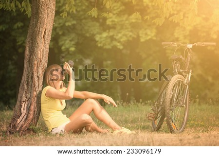Beautiful young woman is drinking a water after cycling in sunny summer day in city park - stock photo