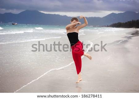Beautiful young woman is enjoying free time at the beautiful sandy beach - stock photo