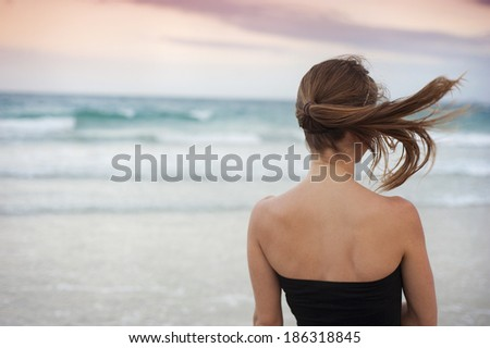 Beautiful young woman is enjoying free time at the beautiful sandy beach - stock photo