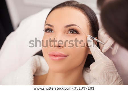 Beautiful young woman is getting botox injection at clinic. She is sitting and smiling. The doctor is holding syringe near her eyebrows carefully - stock photo