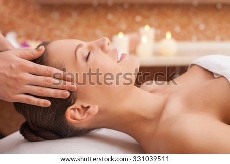Beautiful young woman is getting head massage at spa. She is lying and smiling. Her eyes are closed with pleasure. The female hands of masseuse are massaging her carefully - stock photo