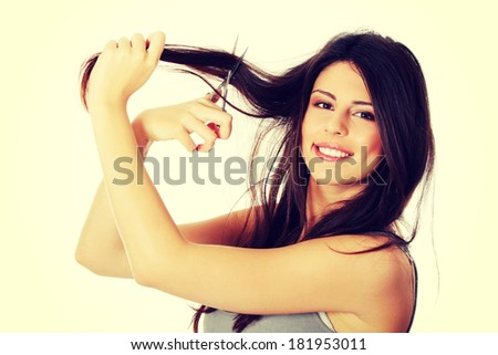 Beautiful young woman is holding scissors. She wants to cut her long hair.  - stock photo