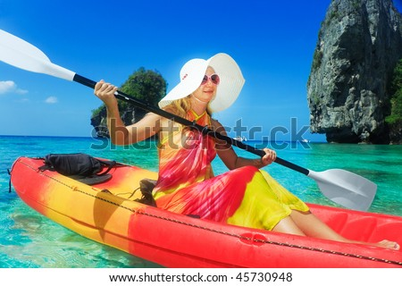 Beautiful young woman is kayaking in tropical lagoon - stock photo