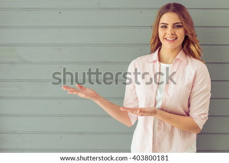 Beautiful young woman is looking at camera, pointing away and smiling, standing against gray background - stock photo