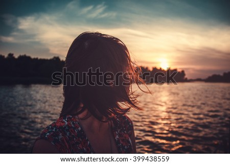 Beautiful young woman is looking at sunset over the river Attractive woman enjoys summer and warm sunlight. She is admiring beautiful view and enjoying sunset sunlight. The wind blew her hair. - stock photo