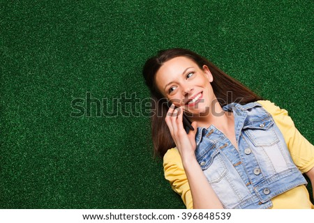 Beautiful young woman is lying on the grass and using phone.Woman using phone - stock photo