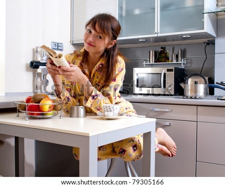 beautiful young woman is reading a book and has a breakfast.