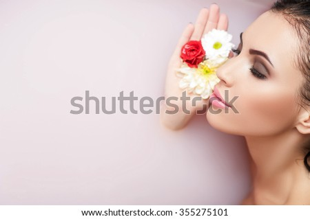 Beautiful young woman is relaxing in bath. She is lying and touching flowers to her face. Her eyes are closed with pleasure. Copy space in left side