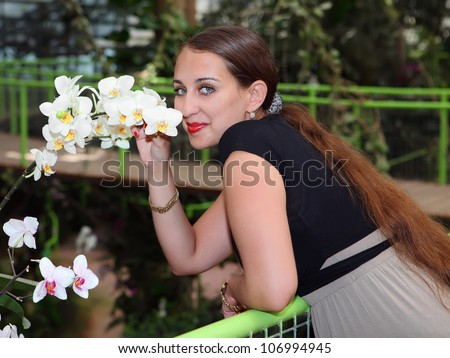 Beautiful young woman is smelling a white orchid in a tropical garden - stock photo