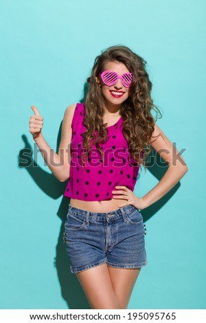 Beautiful young woman is smiling and showing thumb up. Three quarter length studio shot on teal background. - stock photo