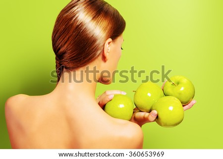 Beautiful young woman is standing back and holding fresh apples over green background. Healthy lifestyle. Healthy eating. Body care. Fruits and vegetables.  - stock photo