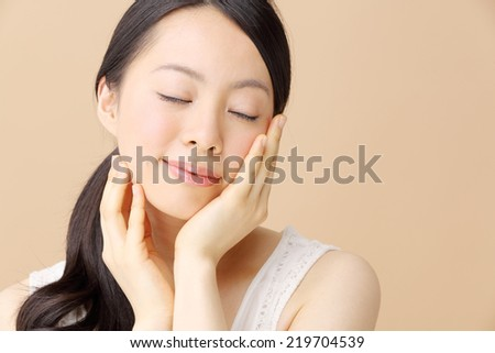 Beautiful young woman isolated on beige background - stock photo