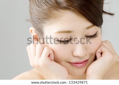 Beautiful young woman isolated on gray - stock photo