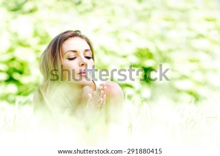 beautiful young woman iwith dandelion lying on grass - stock photo