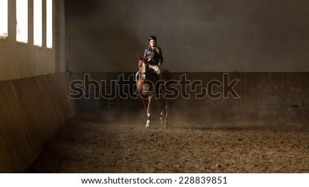 Beautiful young woman jockey doing training at riding hall - stock photo