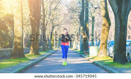 Beautiful young woman jogging alone at park. She is running in the middle of the sidewalk, wearing light blue leggins and a black sweater. Healthy lifestyle and sport concepts. - stock photo
