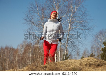 Beautiful young  woman jogging cross country - stock photo