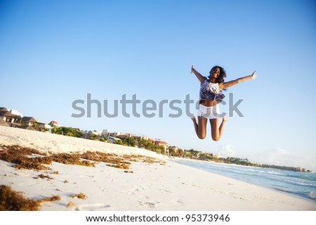 Beautiful young woman jumping at the beach - stock photo