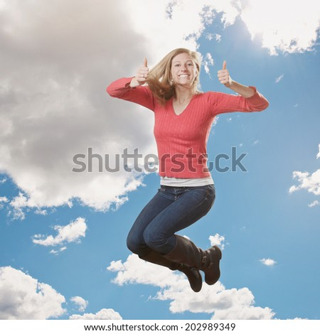 Beautiful young woman jumping giving thumbs up  - stock photo