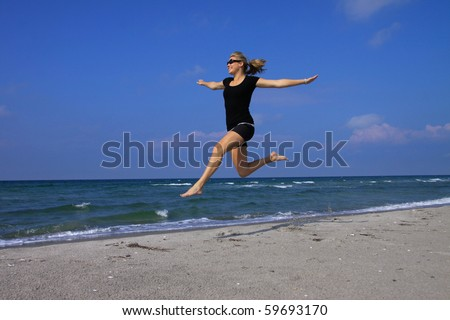 Beautiful young woman jumping gracefully on a deserted beach