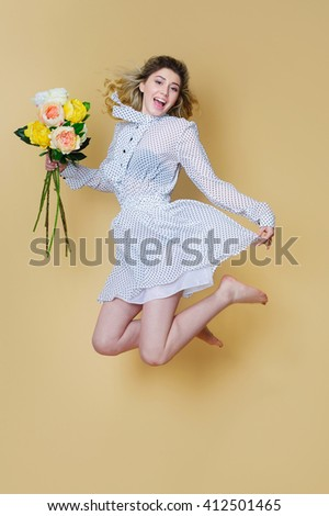 Beautiful young woman jumping happily with flowers bouquet - stock photo