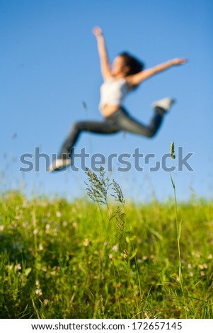 Beautiful young woman jumping on a green grass - stock photo