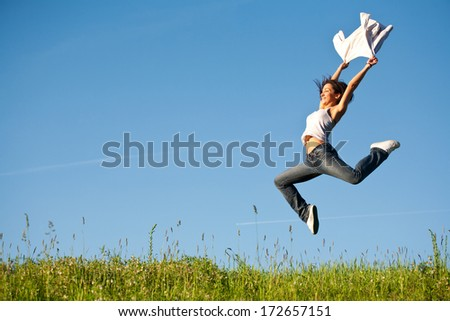 Beautiful young woman jumping on a green grass with a white shirt - stock photo