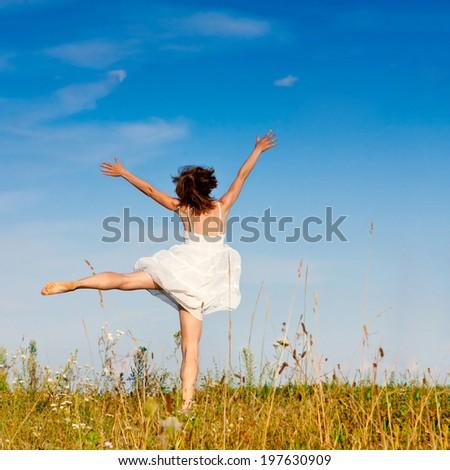 Beautiful young woman jumping outdoors  - stock photo