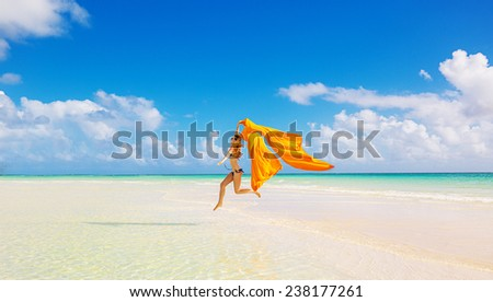 Beautiful young woman jumping running on the beach on a blue sky clouds background. Vacation outdoors leisure happiness joy fun wellness Concept. Healthy active lifestyle vitality. Positive emotions - stock photo