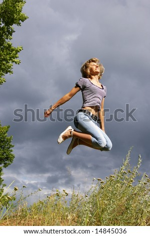 Beautiful young woman jumps. Sky as background