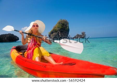 Beautiful young woman kayaking in tropical lagoon - stock photo