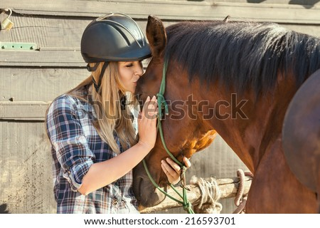 Beautiful young woman kissing her horse - stock photo